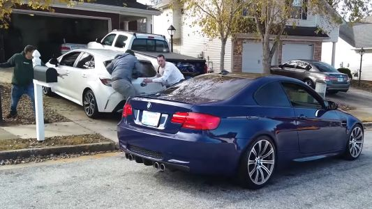 Watch a Toyota Corolla Roll Out Garage and Smash Into BMW M3